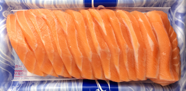 A blue and white tray of raw sliced salmon
