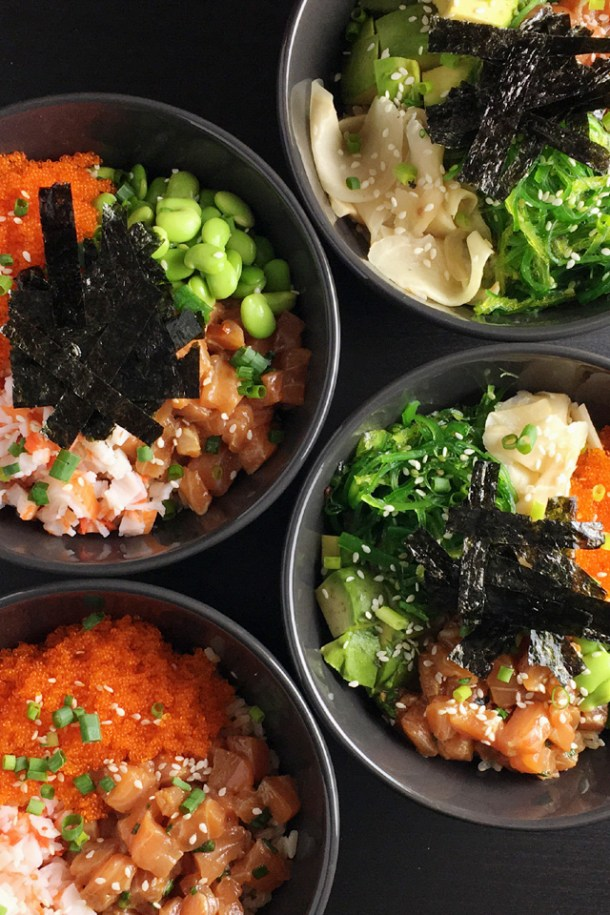 Four bowls of salmon poke bowl with a variety of toppings like edamame beans, tobiko, crab, avocado, pickled ginger, and seaweed.