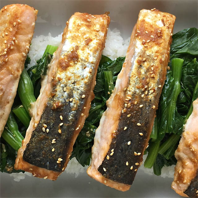 Four broiled miso salmon filets on a bed of white rice and green leafy vegetables