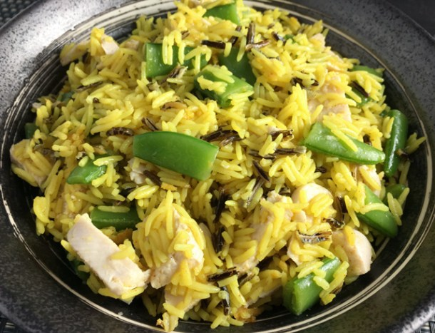 A stone bowl of Chicken Rice Salad containing yellow and wild rice, chopped chicken, and sugar snap peas.