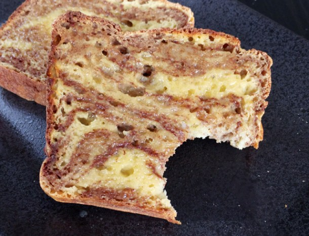 A bite taken out of a buttered slice of Gluten-Free Cinnamon Marble Bread
