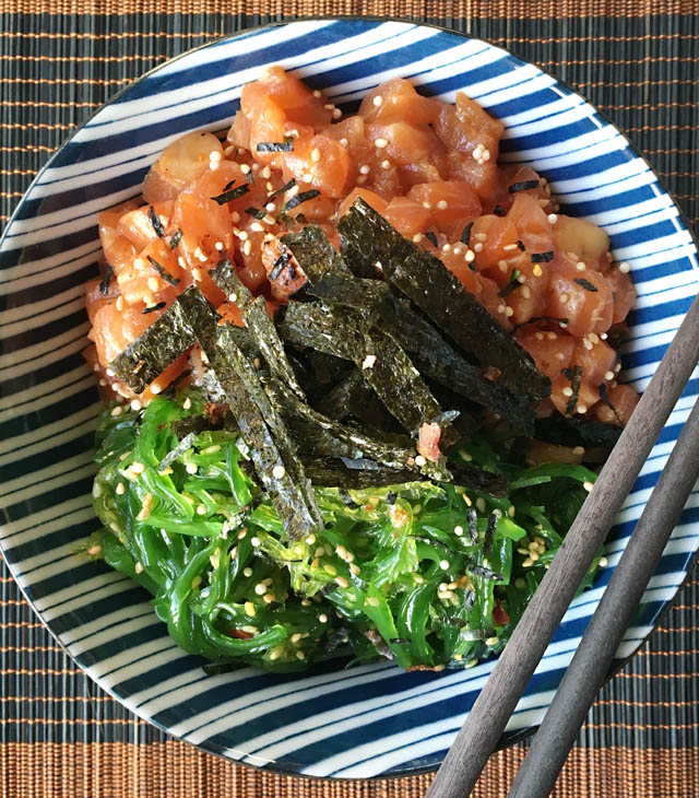A blue and white striped bowl containing chopped fish and shrimp, green seaweed salad, and black dried seaweed strips