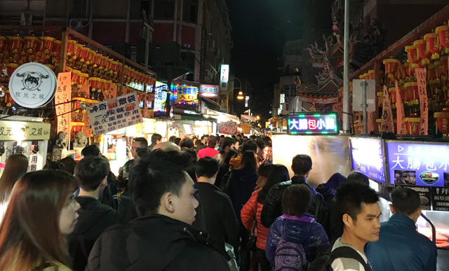 Walking the crowd-filled lane with food stalls at the Shilin Night Market in Taipei
