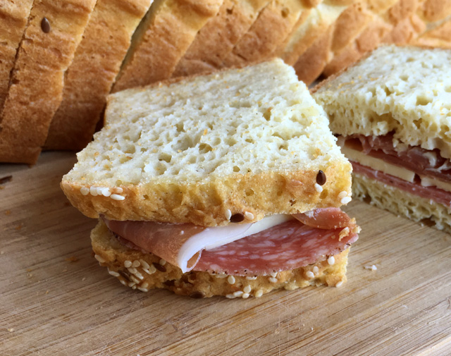A sandwich made of two slices of Soft Homemade Gluten-Free Bread, cheese, and thin sliced meats, all on a wooden cutting board