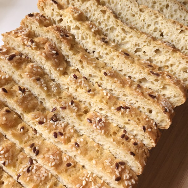 Close-up of sliced golden brown Soft Homemade Gluten-Free Bread with sesame seeds and flax seeds topping