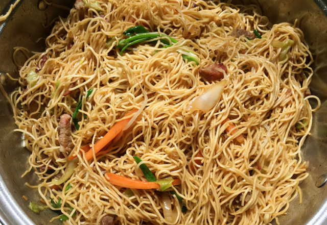 A stainless steel wok containing noodles, green onions, carrots, and pork