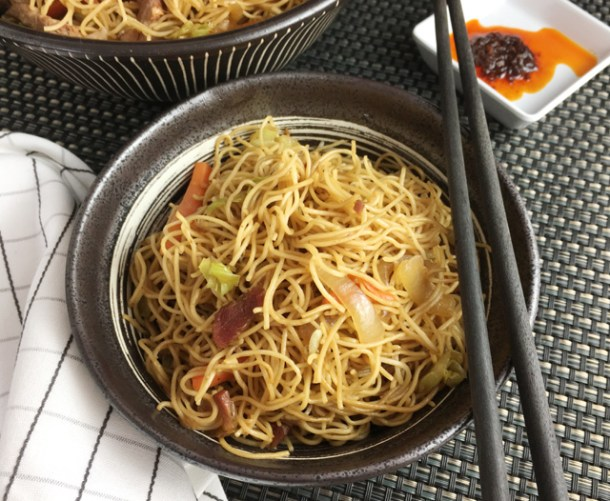 A pair of black chopsticks resting on a bowl containing BBQ pork chow mein
