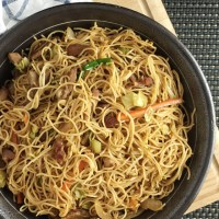 BBQ pork chow mein in a round metallic bowl on a wooden cutting board