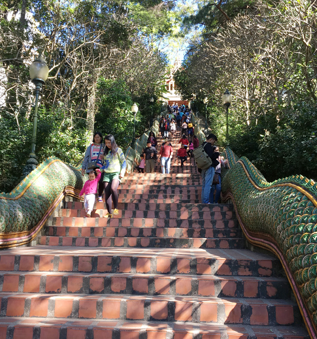 A long staircase with a serpent handrail, leading up to the Golden Temple in Chiang Mai