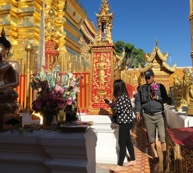 People walking around the Golden Temple in Chiang Mai