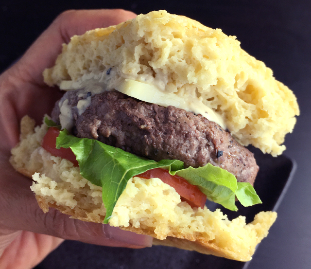 A hand holding a hamburger containing homemade hamburger patty, cheese, tomato slice, and lettuce in a bun