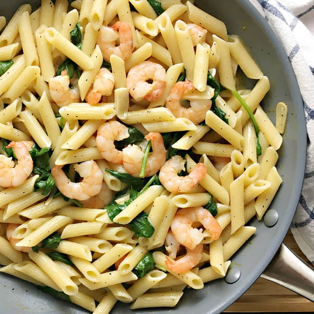Pasta, shrimp, and spinach in a grey frying pan