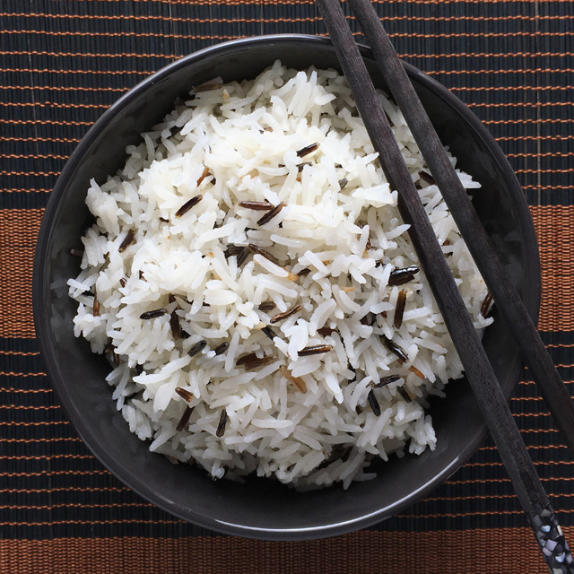 A pair of black chopsticks resting on a dark bowl containing coconut rice