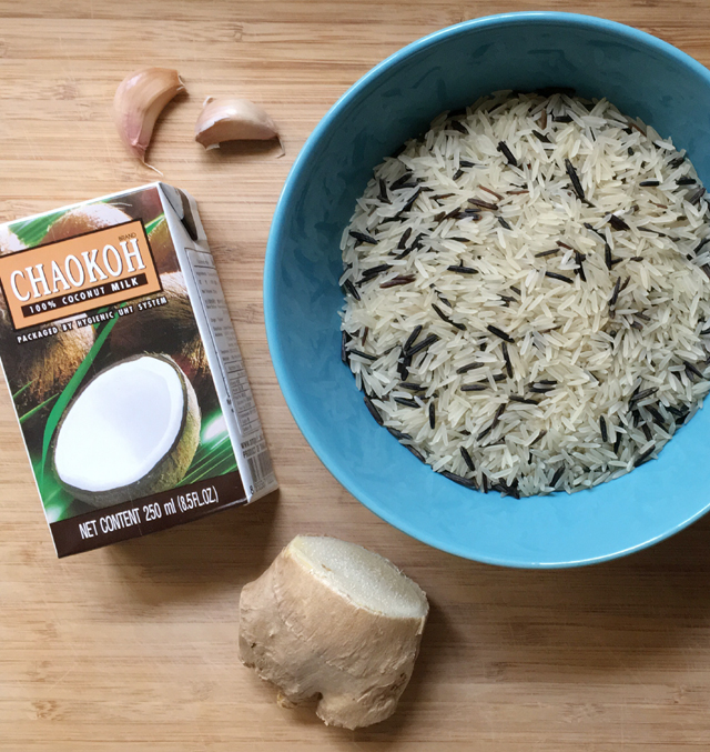 A carton of coconut milk, 2 cloves of garlic, a knob of ginger, and a blue bowl containing basmati and black wild rice, all ingredients for coconut rice