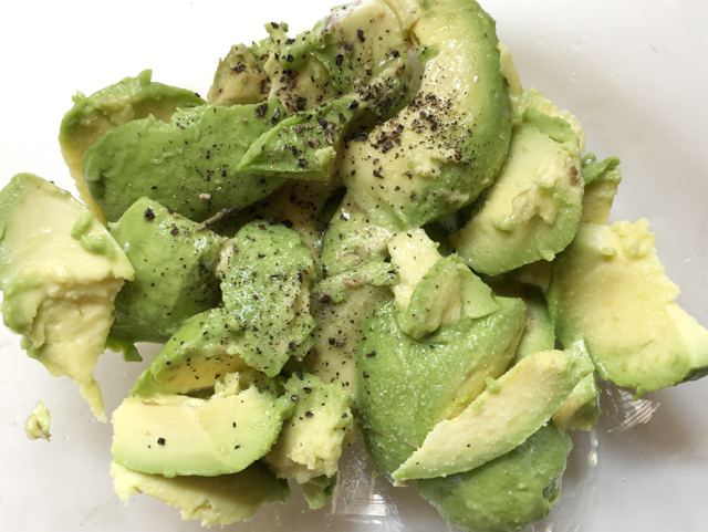 Chunks of avocado sprinkled with white salt and black pepper for super simple basic guacamole