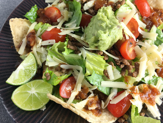 Close-up of a dark round plate containing tortilla chips, ground beef, lettuce, tomatoes, salsa, guacamole, and lime wedges for taco salad