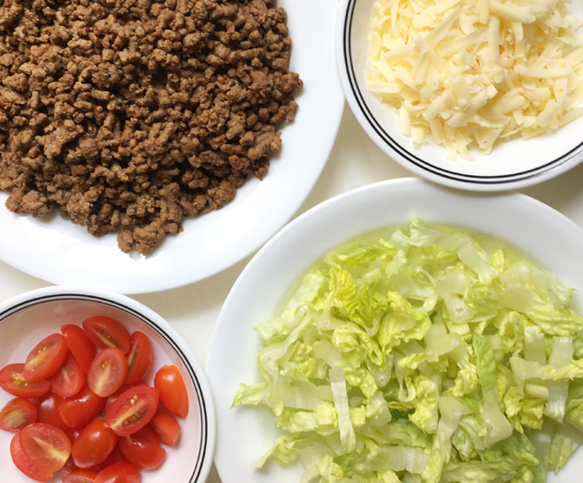 Four white bowls, one containing cooked ground beef, one containing chopped tomatoes, one containing chopped lettuce, and another containing grated cheese for taco salad