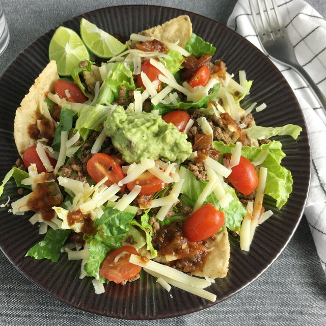 A dark brown plate containing tortilla chips, green lettuce, red tomatoes, ground beef, and cheddar cheese for taco salad