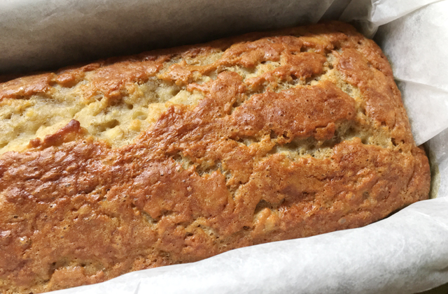 An uncut loaf of moist gluten-free banana bread in a parchment-lined baking pan