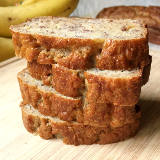 A stack of four slices of moist gluten-free banana bread on a wooden cutting board