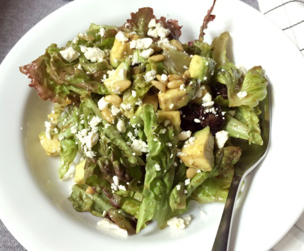 A white round dish containing avocado feta salad tossed with balsamic vinaigrette