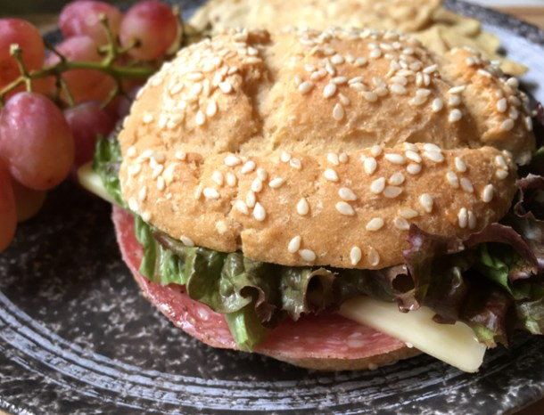 A sandwich containing salami, lettuce, and cheese in a gluten-free bun