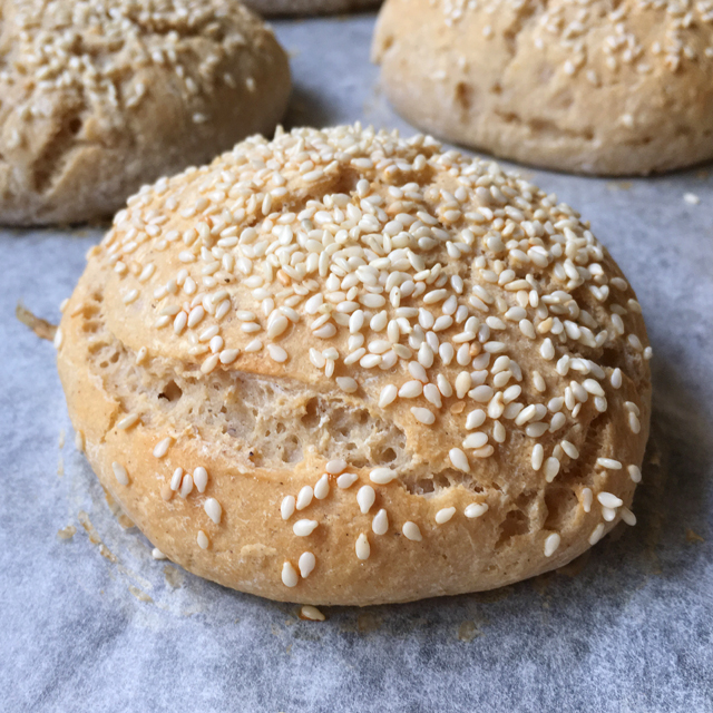 Close-up of a gluten-free bun, topped with sesame seeds and sitting on white parchment paper