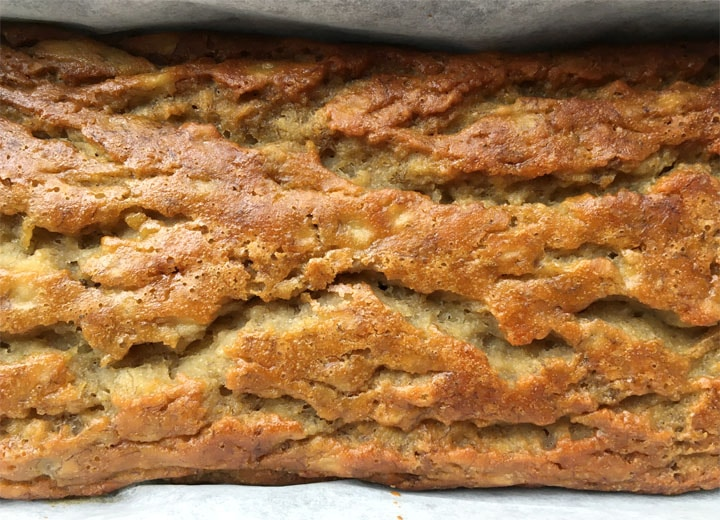 Close-up of a brown loaf of banana bread in a loaf pan