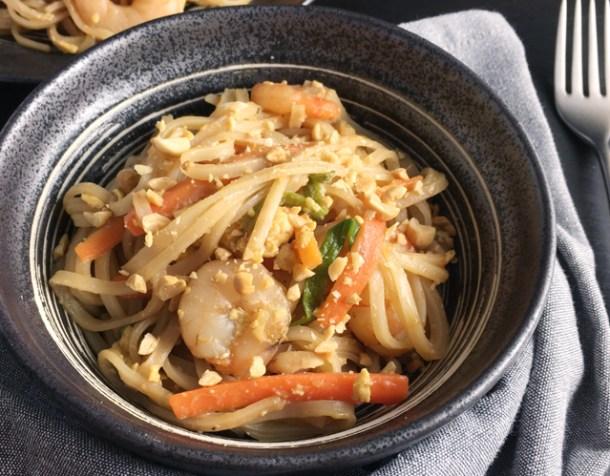 A fork and grey cloth napkin next to a dark round bowl containing shrimp pad thai