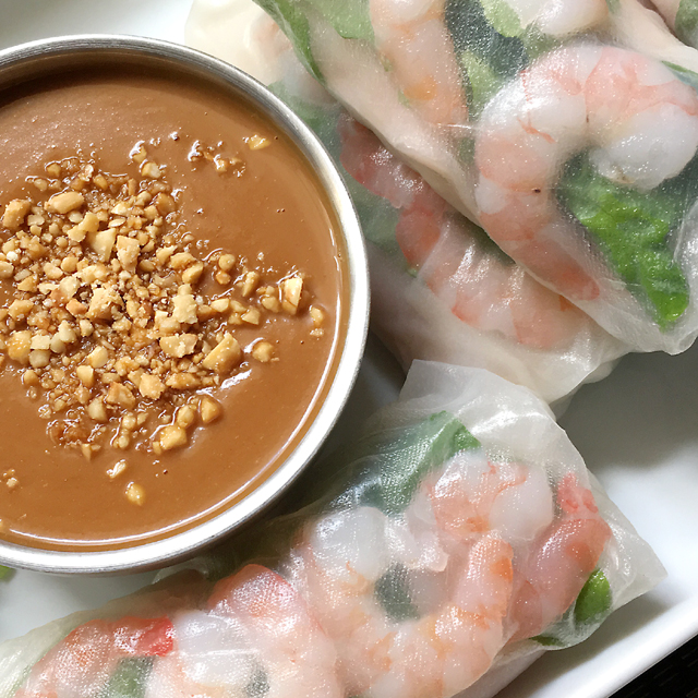 A white dish containing fresh summer rolls and a bowl of peanut sauce topped with chopped peanuts