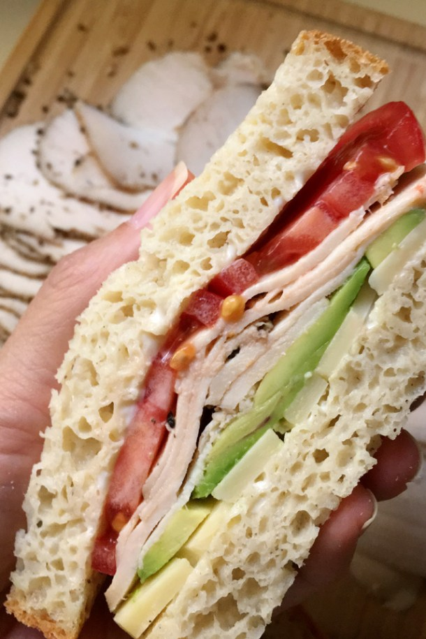 Close-up of a hand holding a sandwich containing roasted chicken deli meat