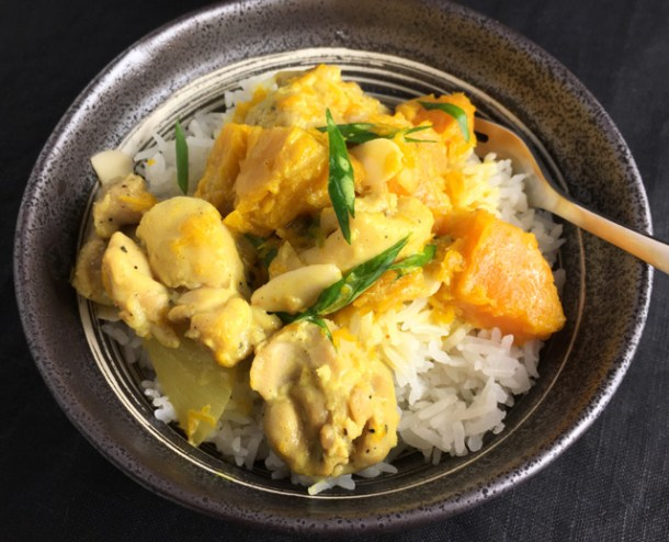 A fork in a metal bowl containing rice and chicken pumpkin curry