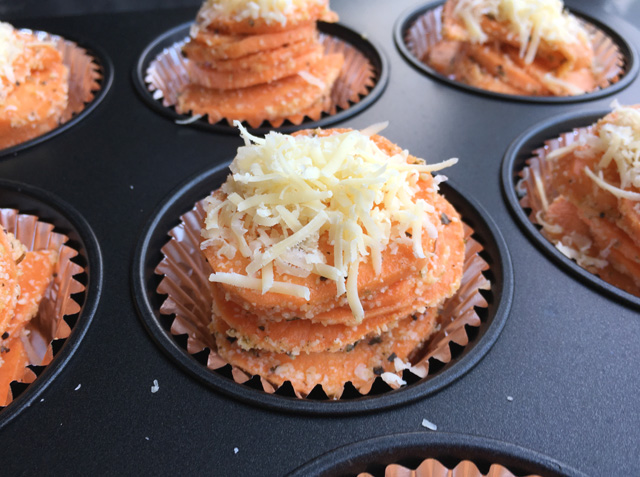 A muffin tin containing uncooked sweet potato stacks topped with grated cheese