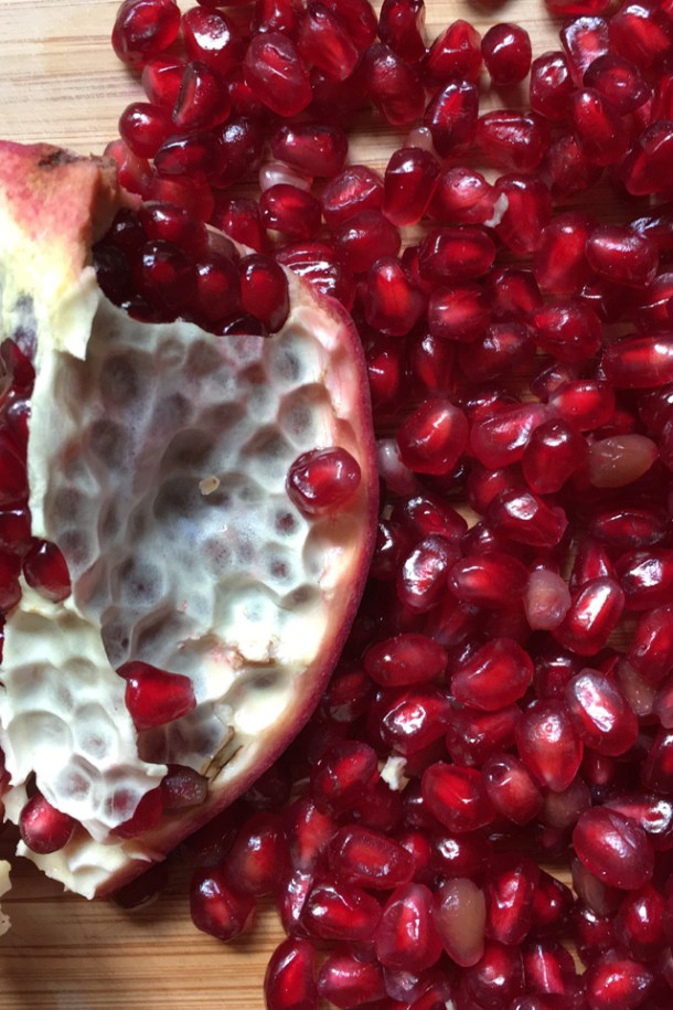 Close-up of a section of pomegranate and pomegranate seeds