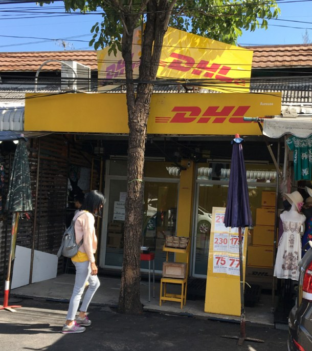A shopfront with a yellow sign that says DHL