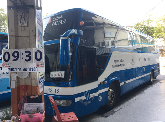 A blue and white bus parked next to a concrete post with a sign saying 9:30