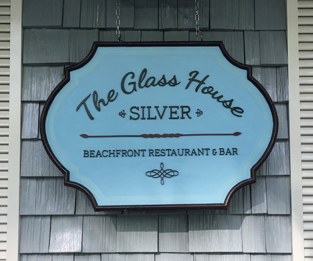 A blue sign that says The Glass House Silver