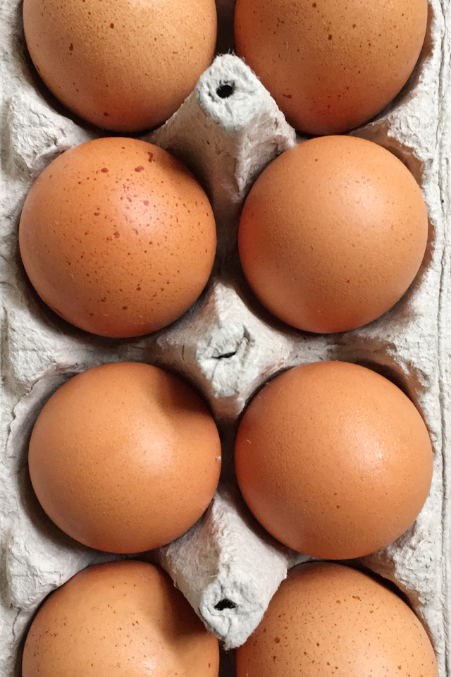 Closeup of 9 brown eggs in a cardboard carton for how to halve an egg