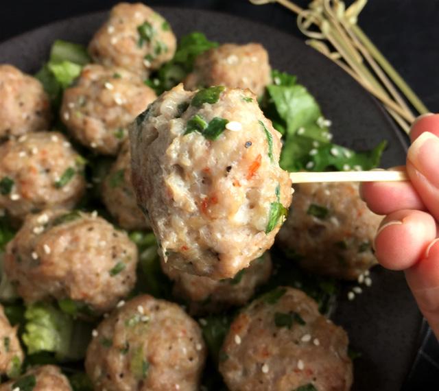 Closeup of a pork and shrimp meatball on a toothpick