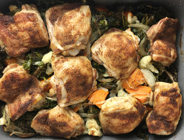 A rectangular pan containing roast chicken and vegetables