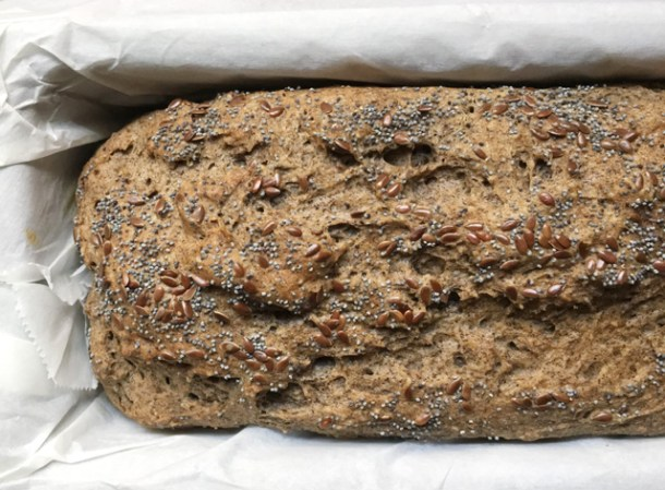 A brown loaf of buckwheat bread in a baking pan lined with white parchment paper