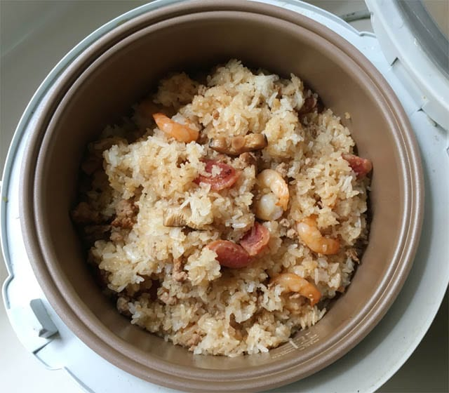 A brown metal pot containing rice, shrimp, mushrooms, and sausages for Chinese sticky rice