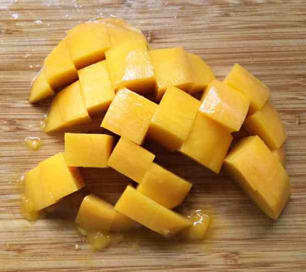 Cubed chunks of yellow orange mango on a wooden cutting board