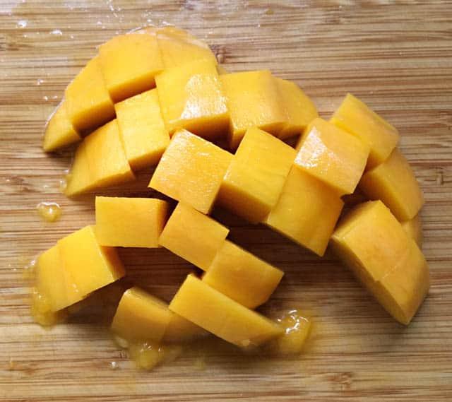 Cubed chunks of yellow orange mango on a wooden cutting board