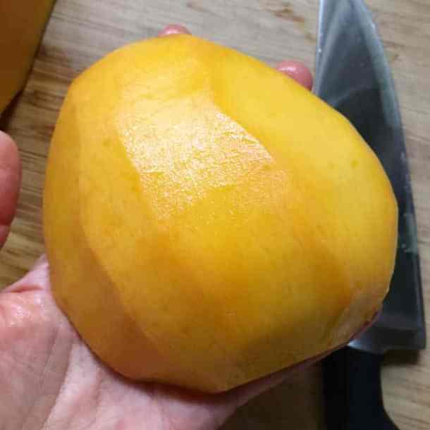 A hand holding a large section of peeled yellow orange mango