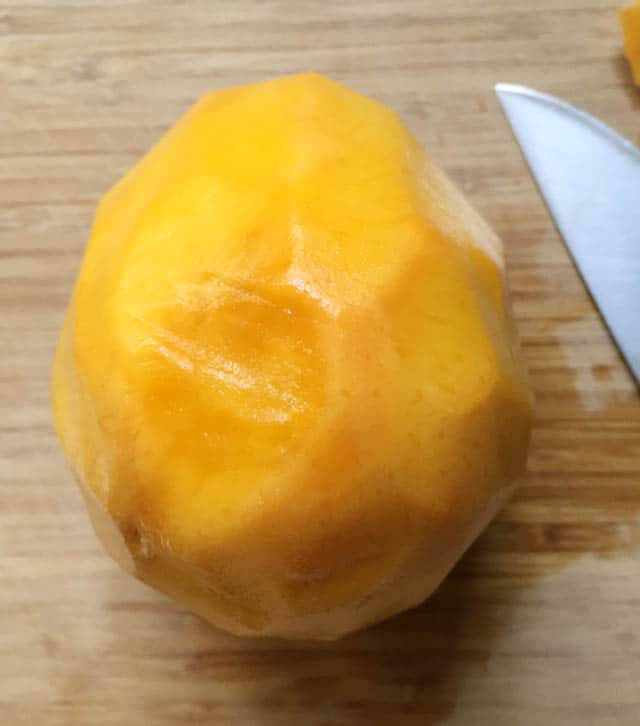 A large yellow orange peeled mango next to a knife on a wooden cutting board