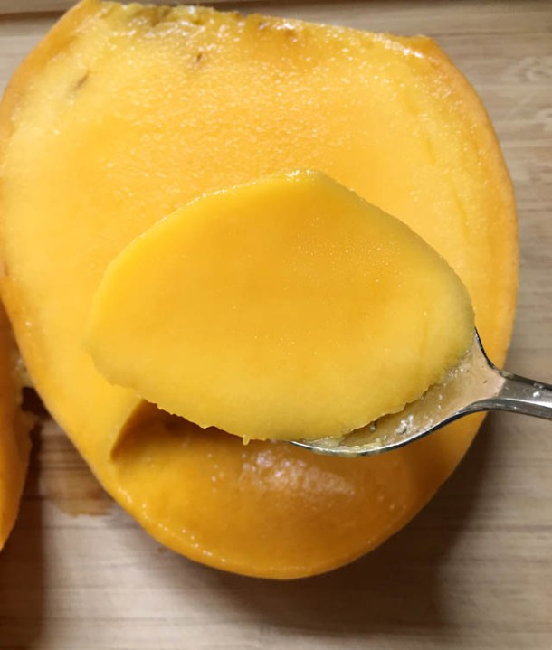 A metal spoon with a chunk of yellow orange mango flesh scooped out from a large section of mango