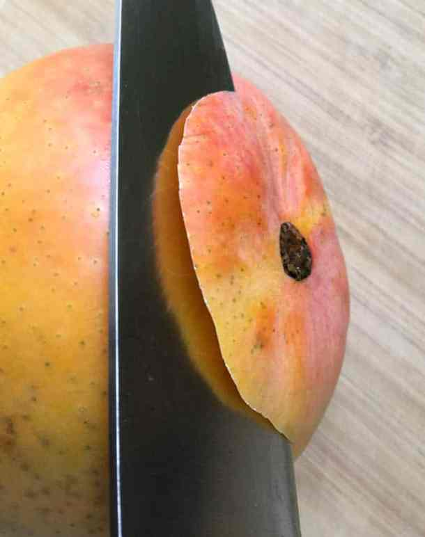 Close-up of a knife slicing through the bottom of a yellow orange mango on a wooden cutting board