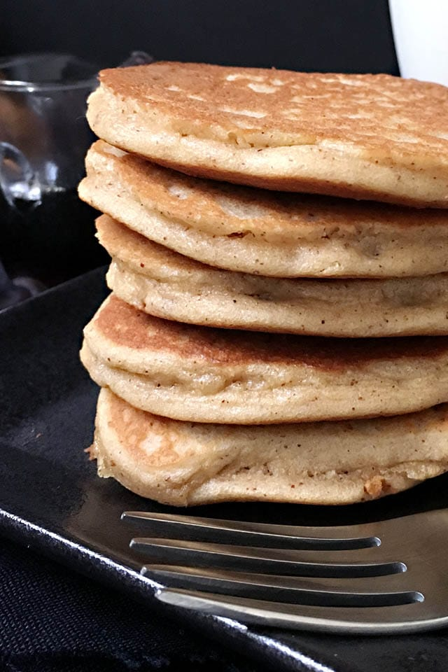 Close-up of a fork in front of a stack of 5 brown almond pancakes on a black plate