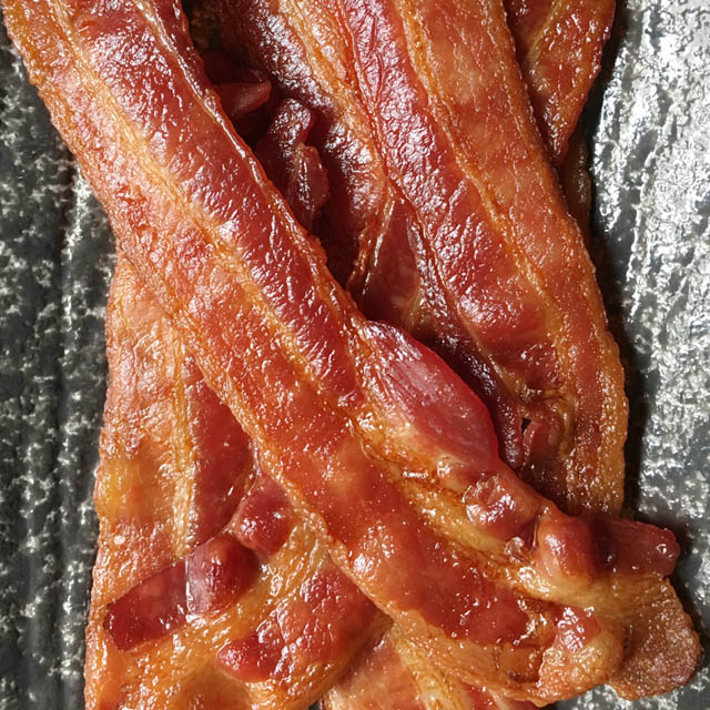 Closeup of cooked bacon strips on a dark grey dish